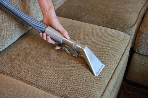 布製ソファに掃除機をかける
